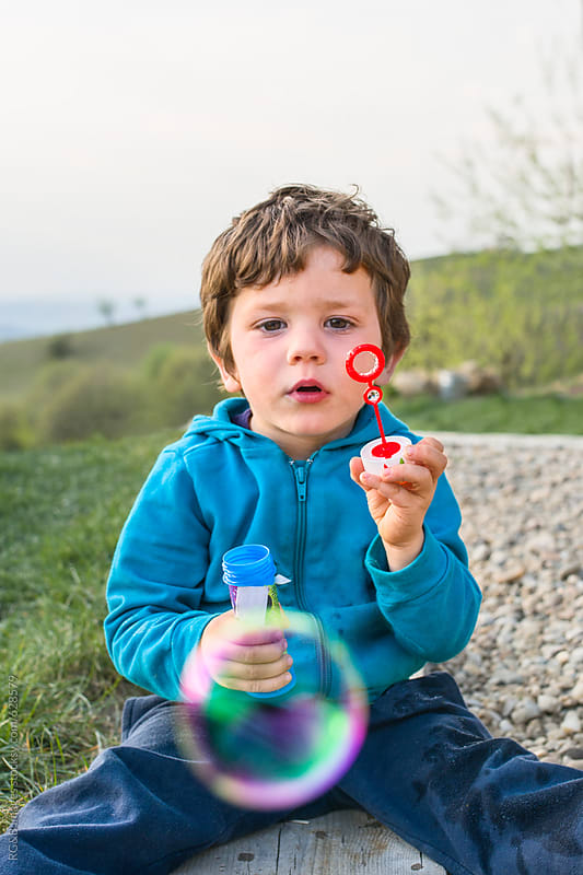 Kid looking at a soap bubble that he just made by RG&B Images for Stocksy United