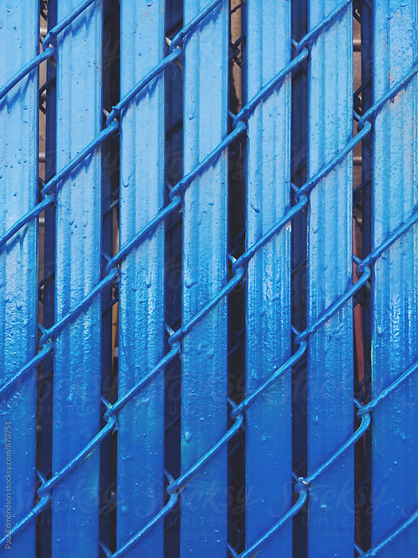 Close up of painted blue chain-link fence by Paul Edmondson for Stocksy United