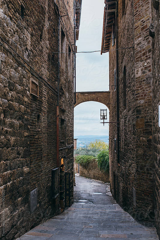 Narrow street with view in San Gimignano, Italy. by Trent Lanz for Stocksy United