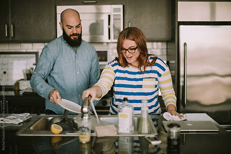 A Young Couple Does Dishes Together in Their Kitchen by Rachel Gulotta Photography for Stocksy United
