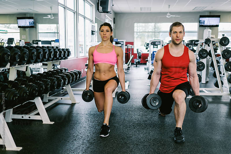 Couple working out together doing lunges  in the gym  by Suprijono Suharjoto for Stocksy United