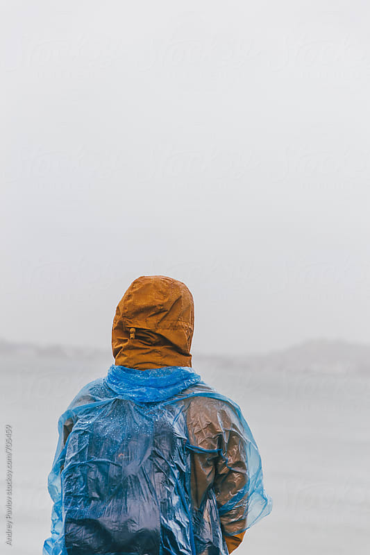 Man covered by raincoat looking at sea by Andrey Pavlov for Stocksy United
