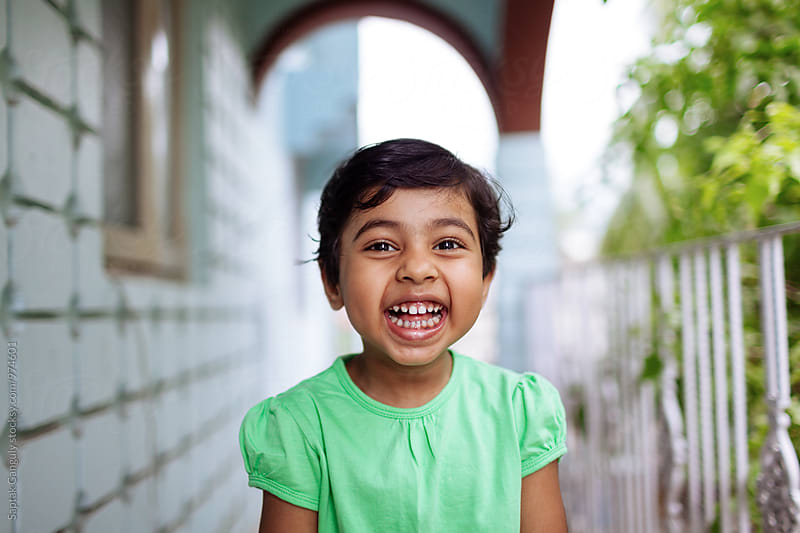 Portrait of cute little girl smiling by Saptak Ganguly for Stocksy United