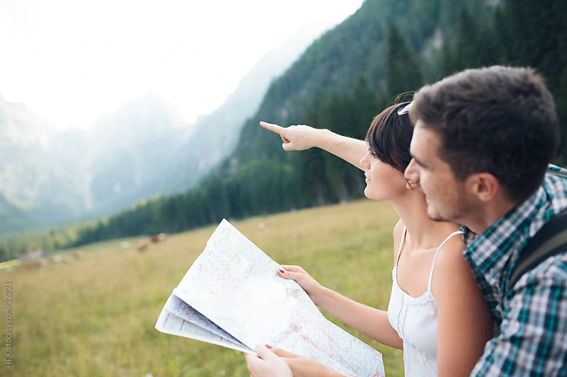 Hiking couple check map for direction by HEX. for Stocksy United