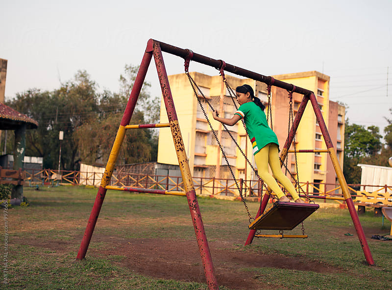 A girl plays and swinging in a park alone  by PARTHA PAL for Stocksy United