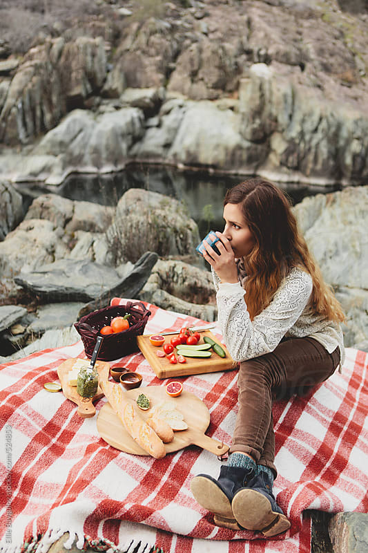 Young woman at a picnic by Ellie Baygulov for Stocksy United
