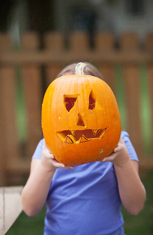 Pumpkins: Girl Holding Up Jack-O-Lantern by Sean Locke for Stocksy United