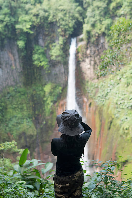 A woman take photo for the waterfall in the rain forest by Song Heming for Stocksy United