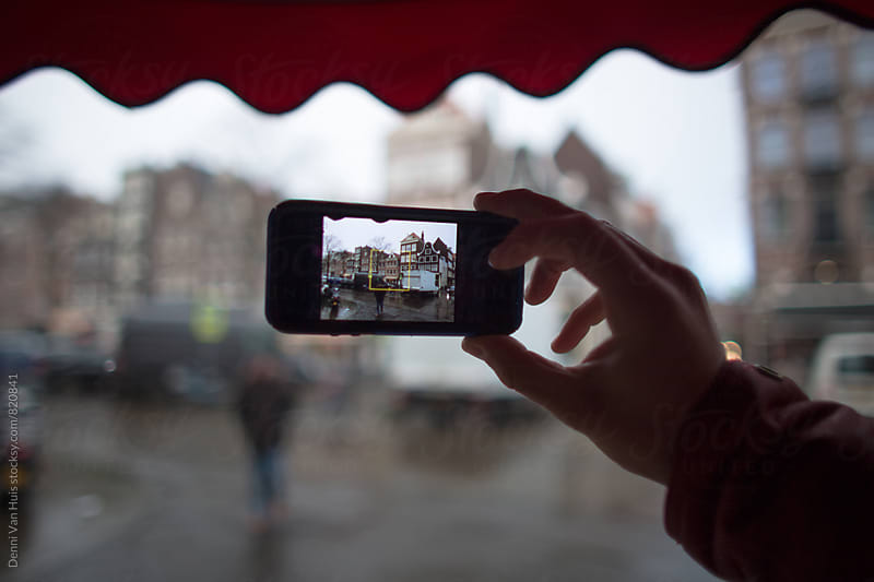 Taking a digital photo with phone on a rainy day in the city by Denni Van Huis for Stocksy United