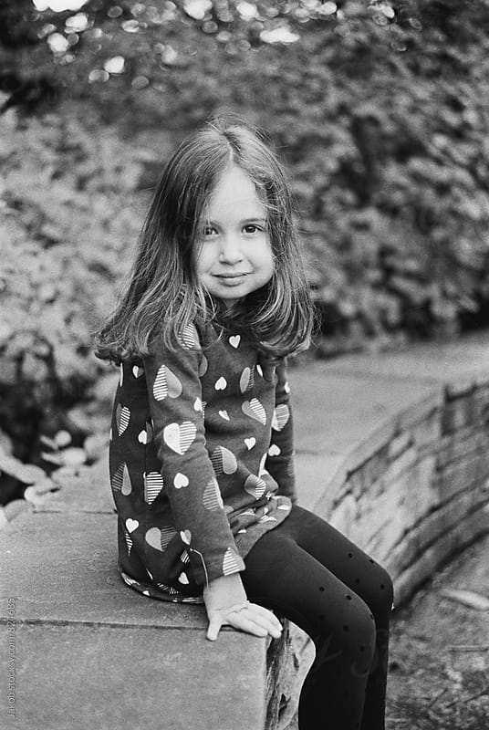 Black and white portrait of a beautiful young girl sitting on a stone wall by Jakob for Stocksy United