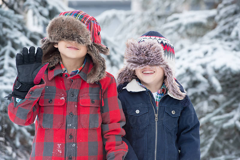 two young children wearing winter hats covering their eyes by Tara Romasanta for Stocksy United