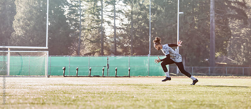 African American athlete  running on a football field by Suprijono Suharjoto for Stocksy United