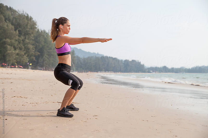Woman doing squats at the beach by Jovo Jovanovic for Stocksy United