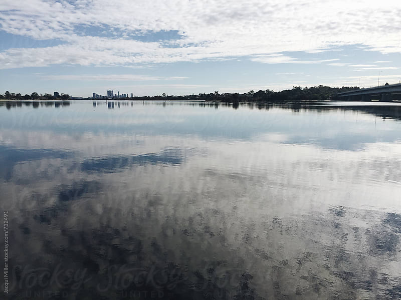 View across Canning River toward Perth city, Western Australia, with cloud reflections on water by Jacqui Miller for Stocksy United