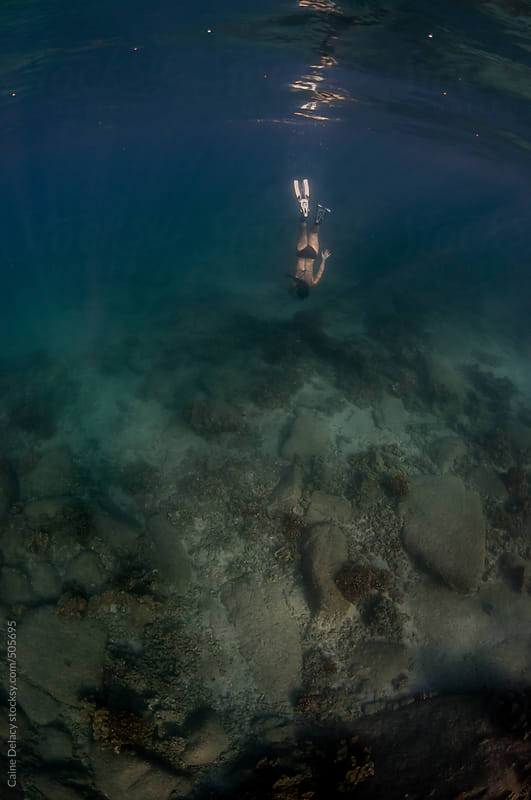 Attractive woman free dives with snorkel to reef by Caine Delacy for Stocksy United