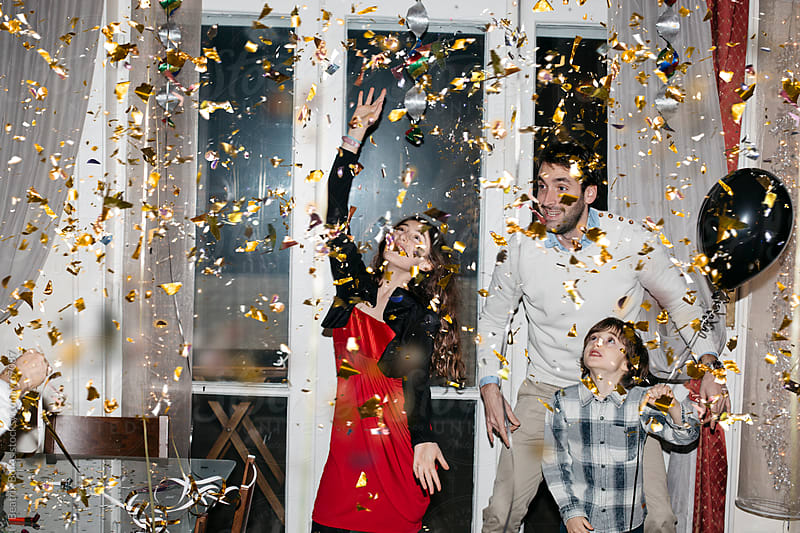 Family dancing together while confetti is thrown by Beatrix Boros for Stocksy United