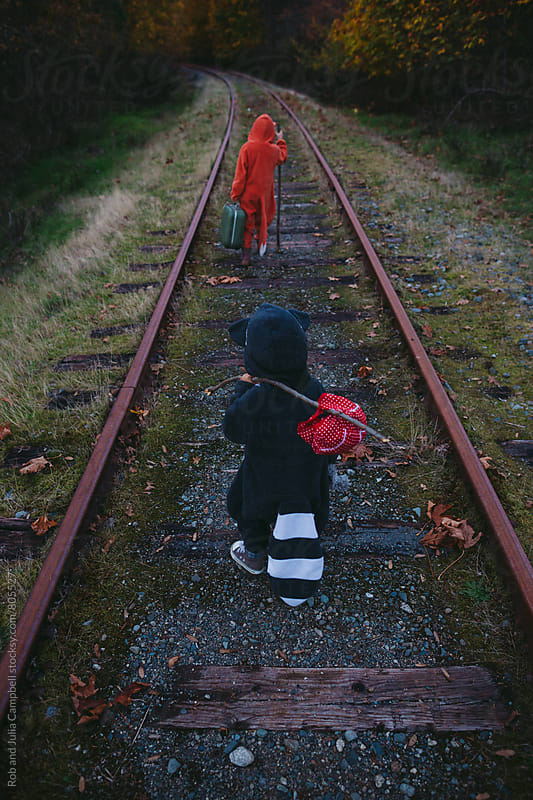 Kids dressed up like fox and raccoon walking on train tracks by Rob and Julia Campbell for Stocksy United