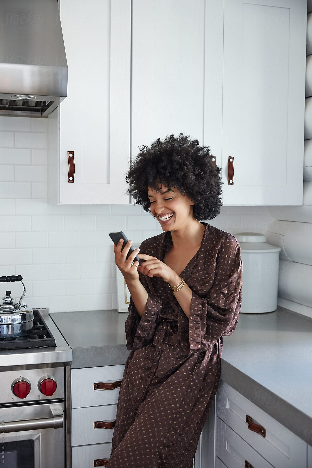 African American Woman On Her Phone In Kitchen Stocksy United