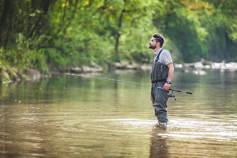 Young Fisherman Exploring the Wilderness in a  Small River by Giorgio Magini for Stocksy United