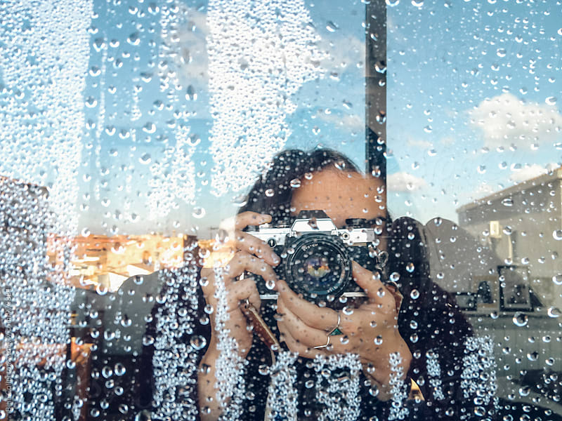 Scene of woman taking pictures through wet window by Jordi Rulló for Stocksy United