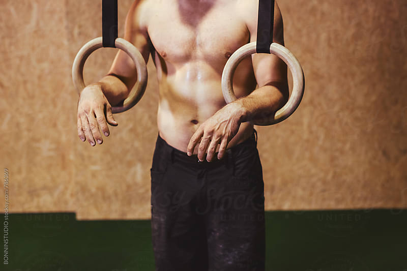 Closeup of a man resting on gymnastics rings in a gym. by BONNINSTUDIO for Stocksy United