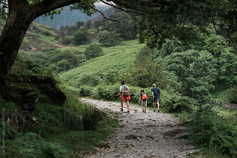 three kids walking on path in the mountain by Léa Jones for Stocksy United