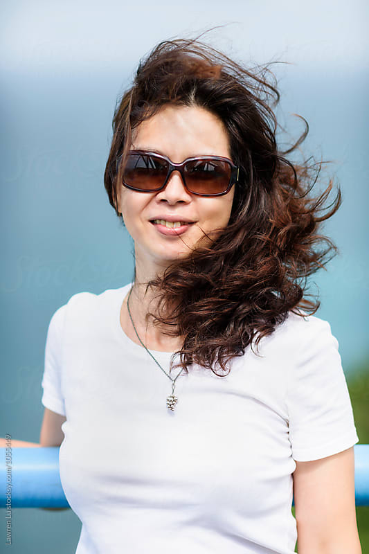 Portrait of Asian woman in sunglasses smiling at camera by Lawren Lu for Stocksy United
