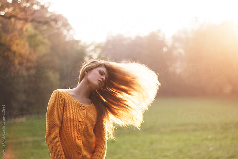 A young woman with her hair flying off to one side by Jovana Rikalo for Stocksy United