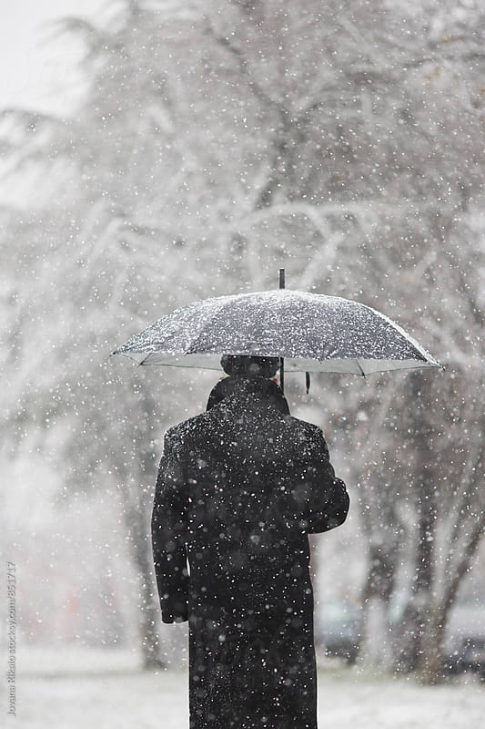 Back view of an elderly man holding umbrella in snowfall by Jovana Rikalo for Stocksy United