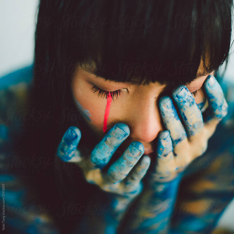 Young woman crying in pink neon paint by Nabi Tang for Stocksy United