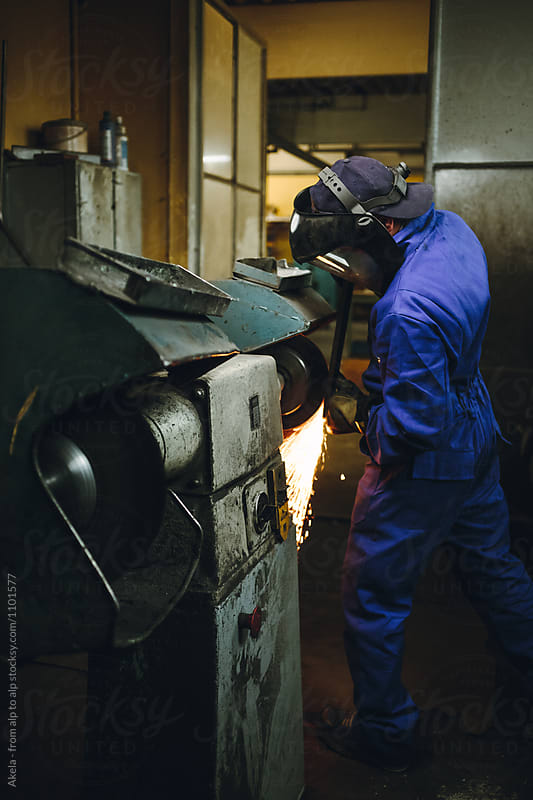 metal worker with protection mask grinding metal plate in a workshop by Leander Nardin for Stocksy United