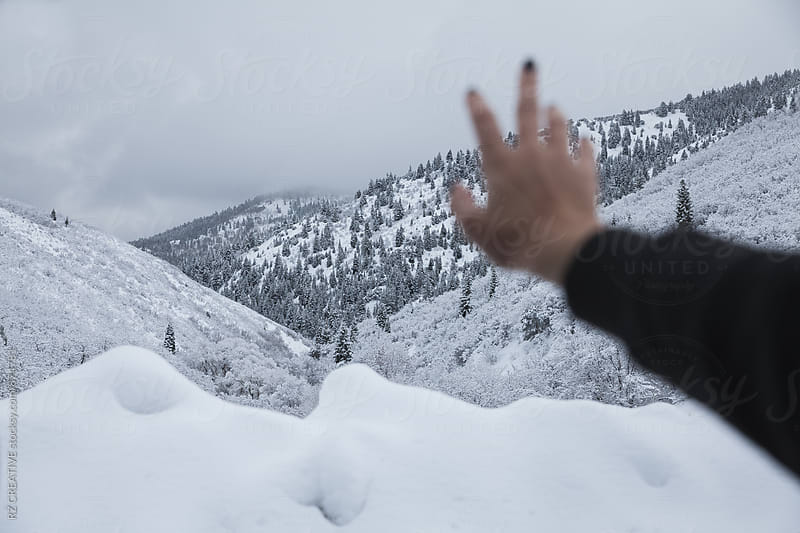 Hand reaching out to snow covered mountains and forest. by RZ CREATIVE for Stocksy United