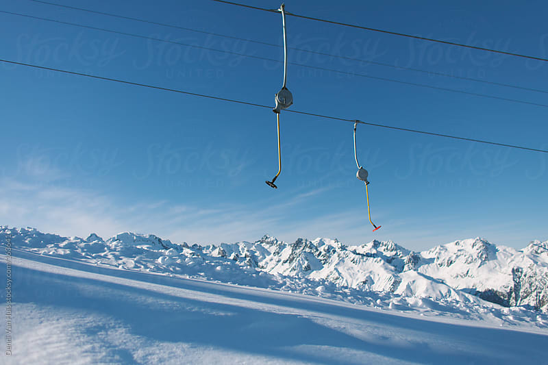 Empty tow ski rope dangling under the blue skies up in the mountains. by Denni Van Huis for Stocksy United