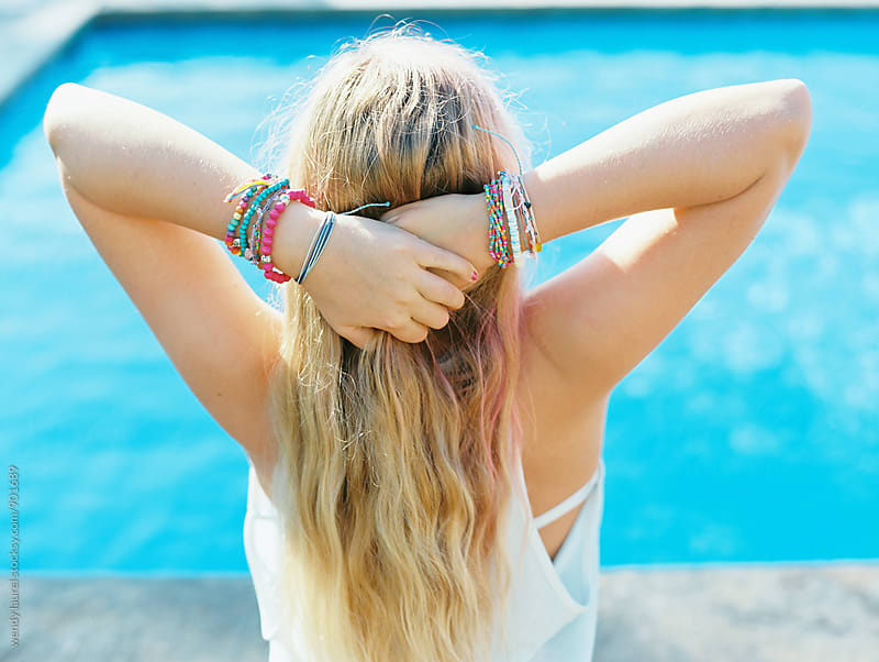 blonde girl at swimming pool with colorful bracelets on wrists by wendy laurel for Stocksy United