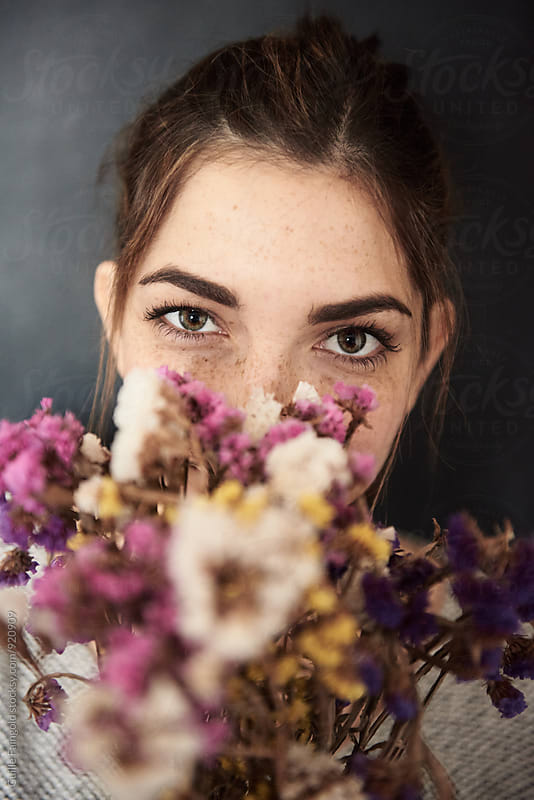 Attractive woman peeping out of bouquet  by Guille Faingold for Stocksy United