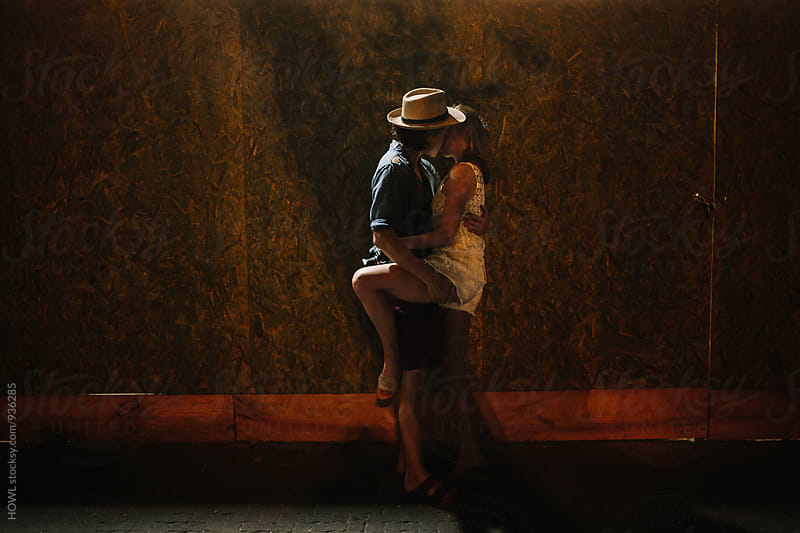 A young couple embraces in a kiss during a quiet moment on the street by HOWL for Stocksy United