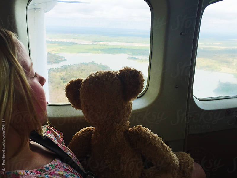 A child and her teddy bear flying in a small plane over Africa  by Helen Rushbrook for Stocksy United