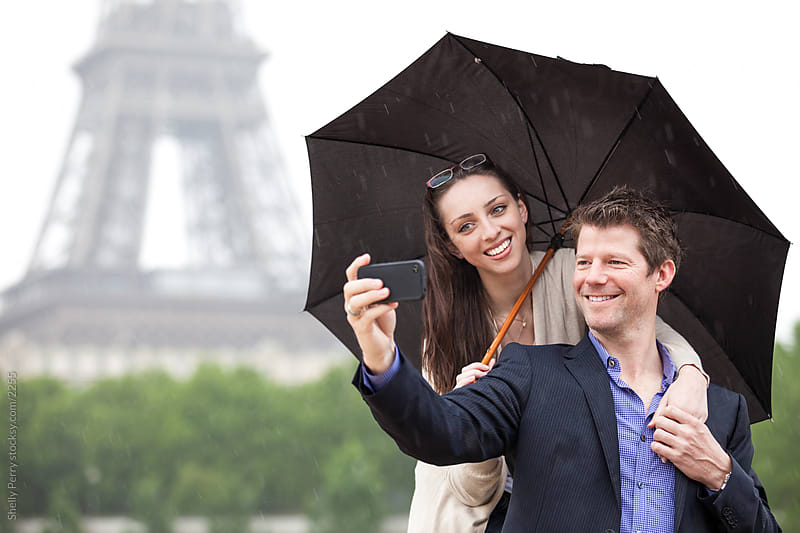 Tourist couple under umbrella in Paris taking a self photo with the Eiffel Tower by Shelly Perry for Stocksy United