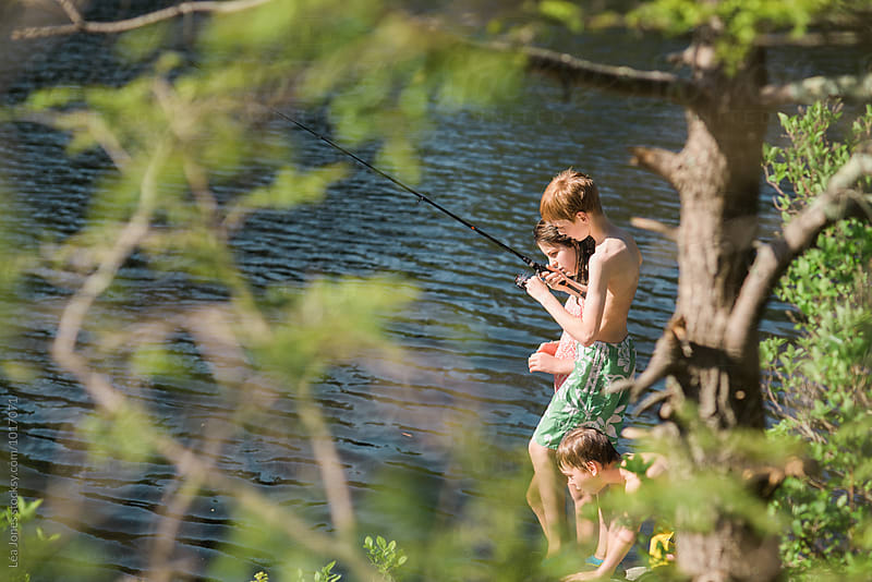 kids fishing on the side of  a lake by Léa Jones for Stocksy United