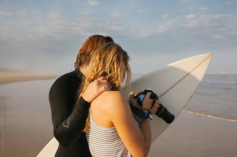 Girl showing her boyfriend the surf photo's she took by Koen Meershoek for Stocksy United
