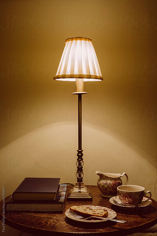 Lamp, books and tea in the evening by Paul Phillips for Stocksy United