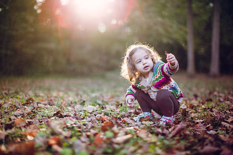 Beautiful toddler holding a leaf in a park by Jakob for Stocksy United