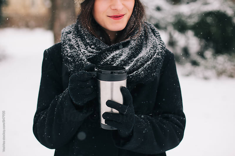 Woman holding a thermos outdoors on a snowy day  by Marija Mandic for Stocksy United