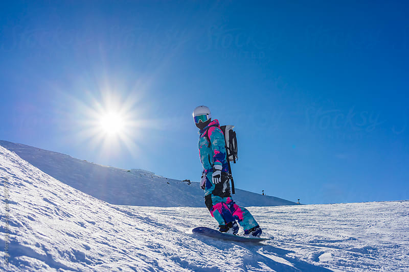 A woman snowboarding at ski area by Song Heming for Stocksy United