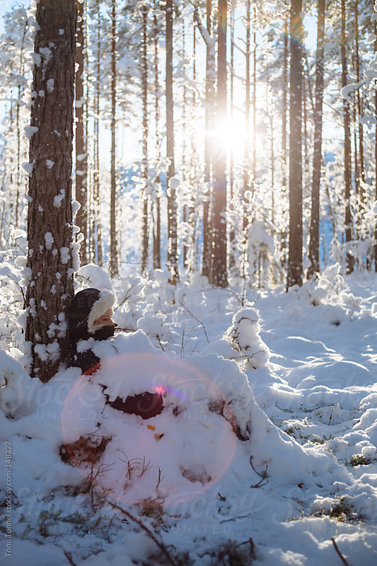 A girl sitting in a winter forest, covered in snow by Tõnu Tunnel for Stocksy United