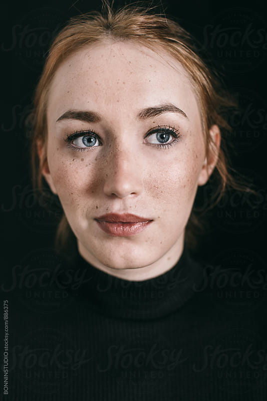 Closeup portrait of a ginger freckled woman on black. by BONNINSTUDIO for Stocksy United