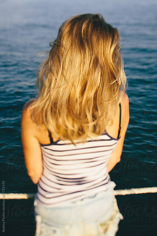Woman looking at the sea, from behind by Andrey Pavlov for Stocksy United