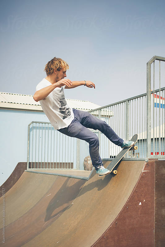 Young man balancing on a rail with his skateboard by Koen Meershoek for Stocksy United