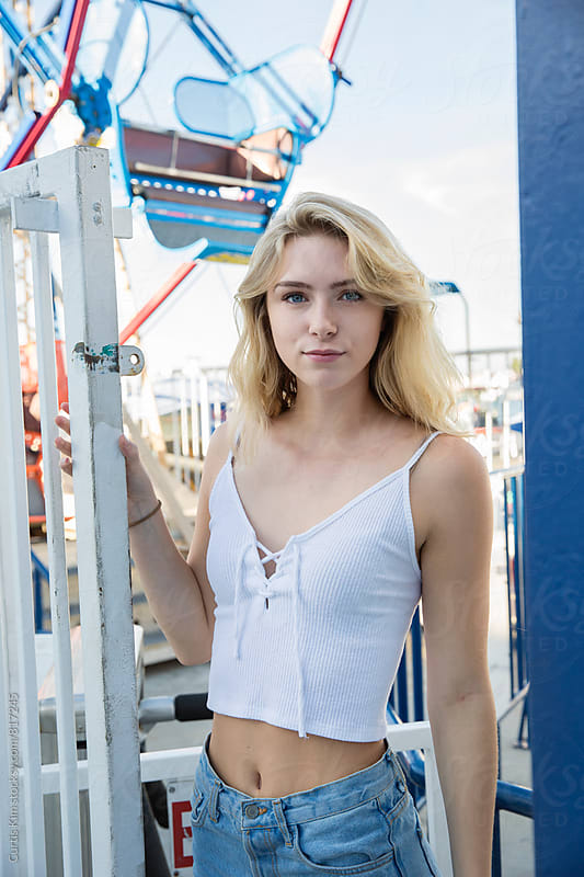 Pretty blonde standing in front of ferris wheel by Curtis Kim for Stocksy United