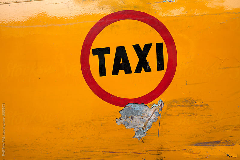 Taxi written in yellow colored bode of a car by PARTHA PAL for Stocksy United